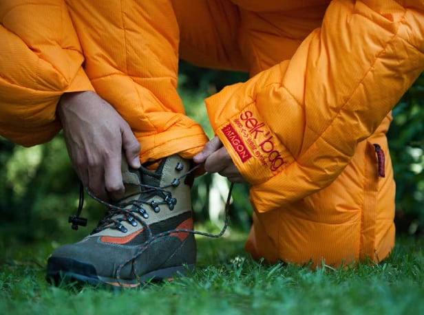 Selk Wearable Sleeping Bag Orange Jacket Man Tying Shoes