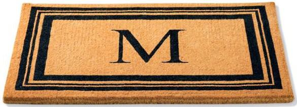 Brown rectangular door mat with black monogram M and line designs